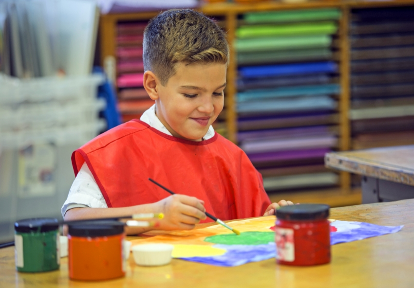 boy painting in art class